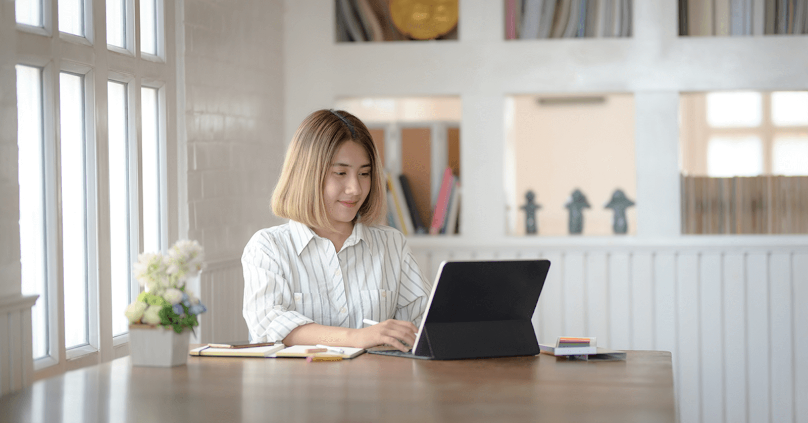 Woman at a desk smiling while looking at her tablet