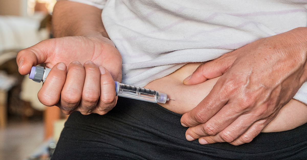 Person injecting insulin at the abdomen