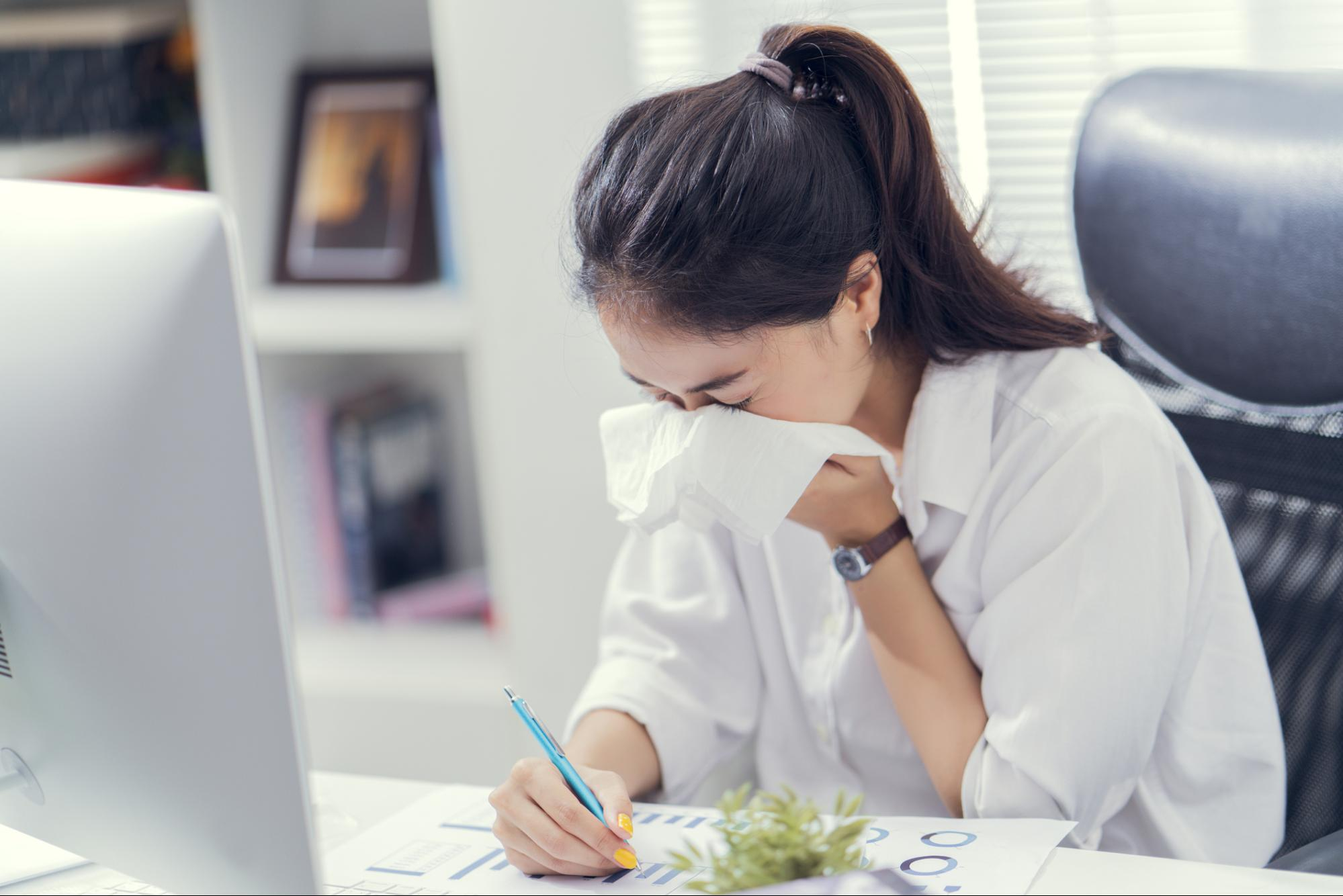 Woman sneezing into a tissue in front of a desk